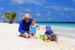 Будьте отцом и 2 дет играя на тропическом пляже Стоковая Фотография RF
