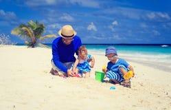 Будьте отцом и 2 дет играя на тропическом пляже Стоковые Фотографии RF