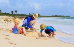 Будьте отцом и 2 дет играя с песком на лете Стоковые Фото