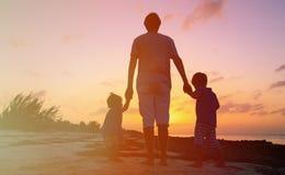 Будьте отцом и 2 дет идя на пляж на заходе солнца Стоковые Фотографии RF