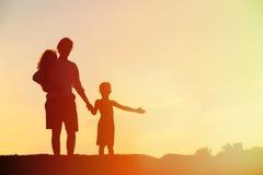 Будьте отцом и 2 дет идя на пляж на заходе солнца Стоковое Изображение