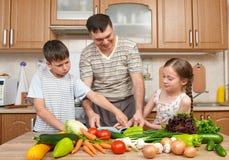 Будьте отцом и 2 дет читая варящ блюда книги и выбора Счастливые семья, девушка и мальчик имея потеху с фруктами и овощами i Стоковые Изображения RF