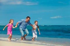 Будьте отцом и 2 дочери бежать на пляже Стоковое Изображение RF