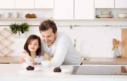 Будьте отцом наблюдать, как его дочь обработала для того чтобы испечь Стоковое Фото