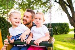 Будьте отцом нажатия его дочерей на качании в парке Стоковое Изображение RF