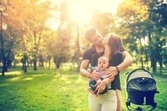 Будьте отцом обнимать мать и держать чувствительное newborn в оружиях Счастье в концепции семьи Стоковые Фотографии RF