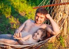 Будьте отцом папы щекоча ребенка дочери ребенк в гамаке Стоковая Фотография
