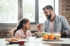 Будьте отцом подавая сварливой дочери с кашой во время завтрака Стоковые Изображения RF