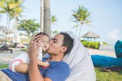 Будьте отцом при его младенец в парке наслаждаясь летом стоковые фото