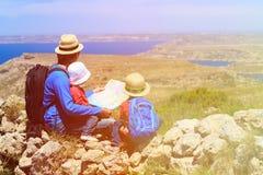 Будьте отцом при дети смотря карту в горах Стоковая Фотография