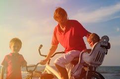 Будьте отцом при 2 дет велосипед на море захода солнца Стоковая Фотография RF
