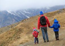 Будьте отцом при 2 дет в горах зимы Стоковые Изображения