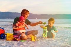 Будьте отцом при 2 дет играя на тропическом пляже Стоковые Изображения RF