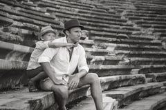 Будьте отцом при сын сидя на античных шагах amfitheater Стоковое Изображение