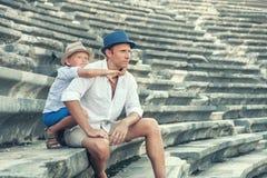 Будьте отцом при сын сидя на античных шагах amfitheater Стоковое Изображение RF