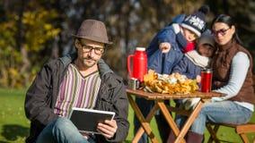 Будьте отцом работы на пикнике с его ПК таблетки Стоковое фото RF