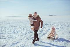 Будьте отцом розвальней его маленькие дочери в дне зимы солнечном стоковые фото
