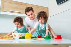 Будьте отцом с близнецами дочерей в варить кухни Папа учит стоковые изображения rf