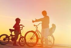 Будьте отцом с 2 детьми на велосипедах на заходе солнца Стоковые Изображения RF