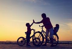 Будьте отцом с 2 детьми на велосипедах на заходе солнца Стоковое Изображение RF