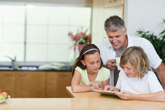 Будьте отцом с дет и таблеткой в кухне Стоковое Изображение