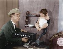 Будьте отцом с младенцем в рожке диктора старого радио (все показанные люди более длинные живущие и никакое имущество не существу Стоковая Фотография RF