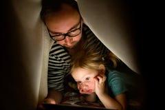 Будьте отцом с таблеткой и маленькой дочерью дома на ноче Стоковое Фото