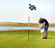 Будьте отцом уча дочери для того чтобы сыграть гольф на установке на зеленый цвет стоковое изображение