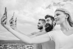 Был самовлюбленный Люди наслаждаются стрельбой selfie на естественном ландшафте Сексуальная женщина и люди держа смартфоны в рука стоковые изображения rf