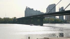 Быстрая быстрая моторка быстро двигая плавать на реку к мосту Промышленный город на предпосылке сток-видео