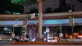 Быстрое движение MRT и автомобилей проходя дорогой на ноче