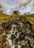 Быстроподвижный поток бежать вниз с холма с облаками и деревьями как предпосылка стоковые фотографии rf