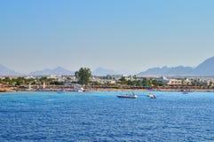 Быстроходный катер с побережья, море, пляж, отпускники, здания, против фона гор и неба Стоковая Фотография