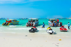 Быстроходные катера, jetski и турист на пляже стоковое изображение rf