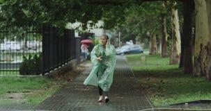 Быстро бежать молодое ladie на день дождя держа цветок и нося плащ видеоматериал