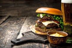 Быстро-приготовленное питание Большой бургер с говядиной и стеклом пива Стоковые Изображения