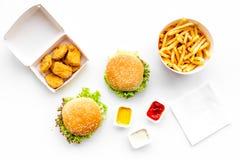 Быстро-приготовленное питание Наггеты Chiken, бургеры и фраи француза на белом взгляд сверху предпосылки Стоковые Фотографии RF