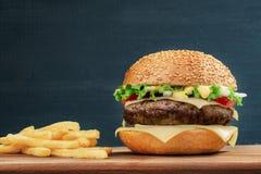 Быстро-приготовленное питание Cheeseburger и француз жарят на деревянной доске, на темной предпосылке Стоковые Фото