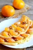 Быстрый омлет яичка Здоровый омлет с tangerines и грецкими орехами на плите Свежие tangerines, ткань мешковины на старой деревянн Стоковое Изображение RF