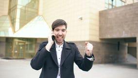 Быть съемка тележки молодого бизнесмена говоря на smartphone и танцующ после делать дело идет около офисных зданий