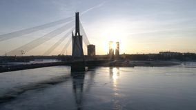 Былинный мост снял с движением и заходом солнца за зданиями 4K 50FPS акции видеоматериалы