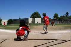 Бэттер ударяя шарик с улавливателем за им. Стоковое Фото