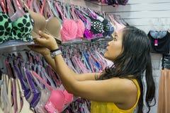 Бюстгальтер азиатской девушки покупая на магазине Стоковые Изображения RF
