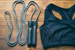 Бюстгальтер спорт и веревочка скачки на деревянной предпосылке Стоковое Фото