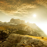 Благоустраивайте Италию, доломиты - на лошади запятнанной восходом солнца пася самостоятельно на утесах Стоковое Изображение