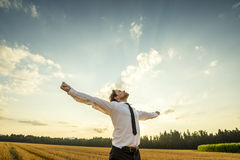 Благодарный бизнесмен с открытыми оружиями на поле стоковое изображение