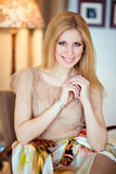 Блестящая белокурая девушка в чувствительном платье усмехается, сидящ в A.C. стоковое изображение rf