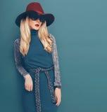 Блестящая белокурая модель в винтажной шляпе и платье на зеленом backgrou Стоковое Изображение