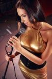 Блестящая девушка поя на этапе стоковые изображения rf