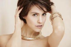 Блестящая женщина в ювелирных изделиях золота Стоковое фото RF